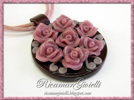 Ciondolo ed orecchini realizzati in quilling e decorati con piccole rose in porcellana fredda