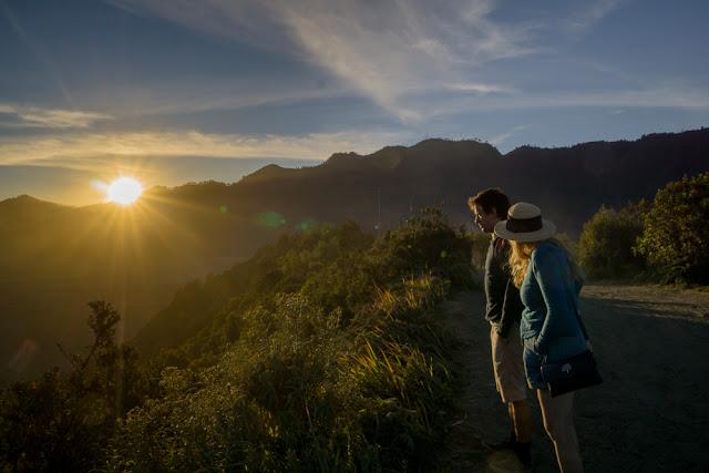 Sepasang turis menikmati sunset di mentigen bromo