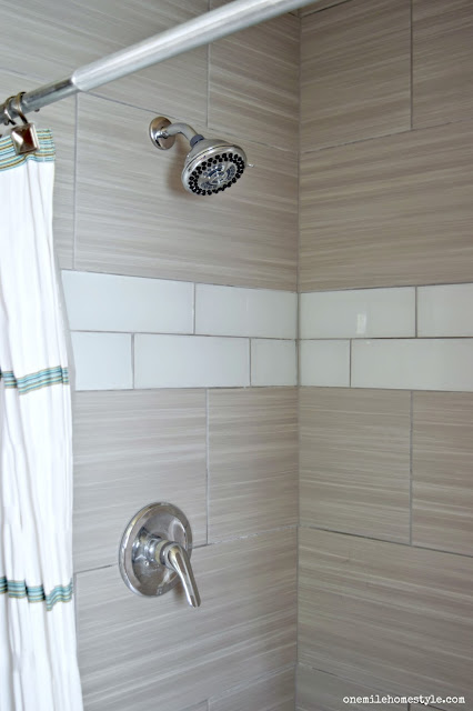 Waterpik showerhead in a grey and white tiled shower.