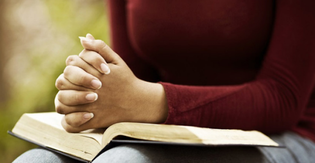 Berdoa sambil memegang alkitab