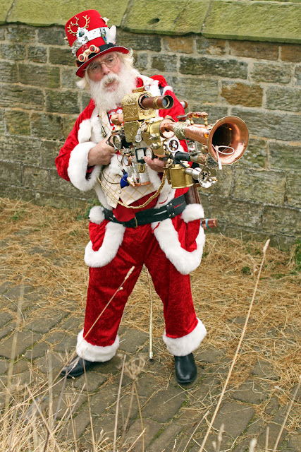 Man dressed as Steampunk Santa Claus cosplay. Santa costume with steampunk trombone/gun, waistcoat, top hat and goggles. Steampunk Christmas costume