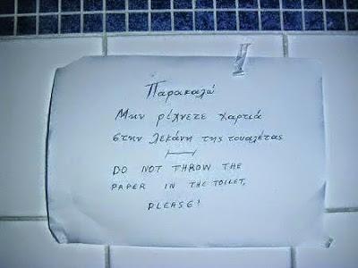 Biała kartka z napisaną w języku greckim informacją nie wrzucać papieru do klozetu.