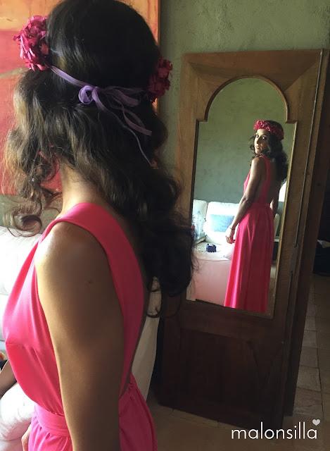 Invitada a boda con vestido largo fucsia y escote en la espalda reflejada en el espejo con corona de flores preservadas en buganvilla