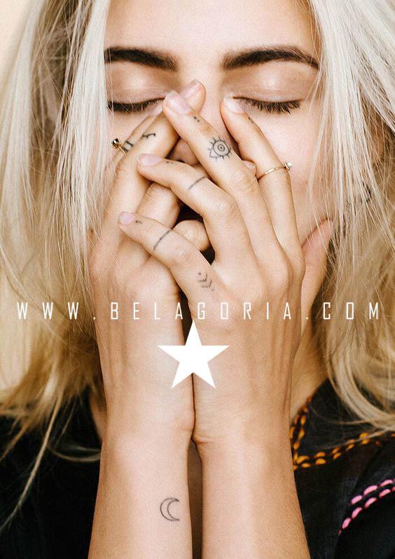 Foto de modelo tapandose la cara, lleva tatuaje pequeño en la muñeca