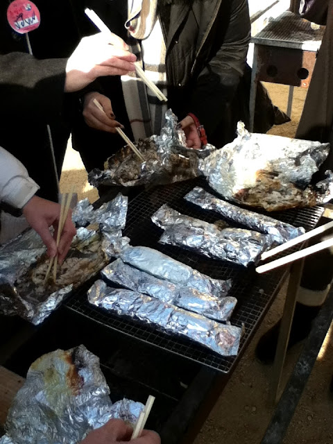 Eating grilled fish with chopstickes at The Hwacheon Ice Festival in Korea | Lindsay Eryn