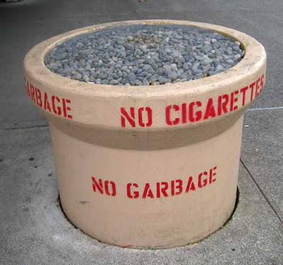 Large concrete cylinder, about three feet tall, full of round rocks, stencil letters on the side saying No Cigarettes No Garbage