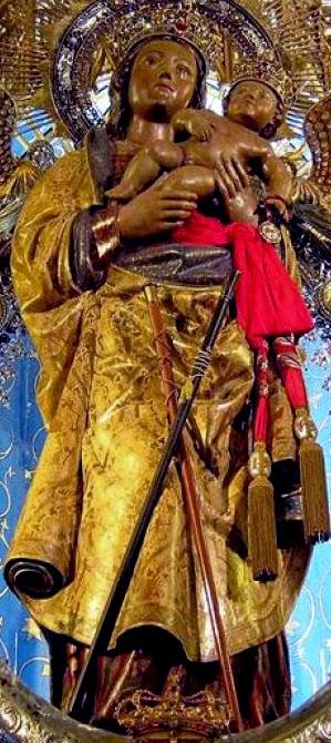La Virgen de la Almudena es una escultura de madera bien tallada, con pliegues en sus ropajes dorados y un fajín rojo. Está de pie y sostiene al niño cerca de su cara.