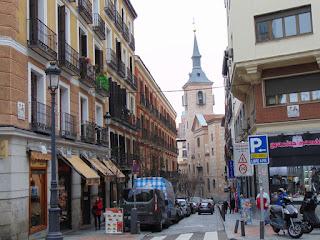 Vista desde la calle Mayor, Tradicionales edificios de viviendas de cuatro plantas con balcones. Al fondo la iglesia de San Ginés y su torre con chapitel.