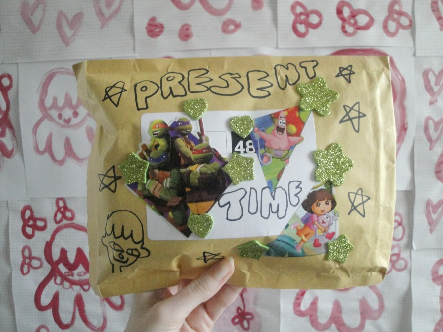 "The front of the jiffy bag, which is also decorated with drawings Nickolodeon stickers, and bubble writing that says ""present time""."