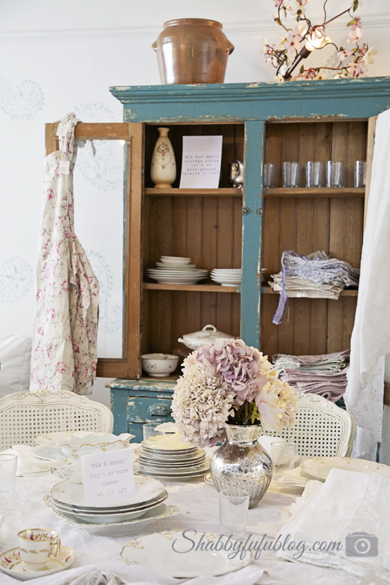 A beautiful shabby chic style tablescape with white china and linens and a distressed blue china cabinet - both from Shabby Chic Couture.