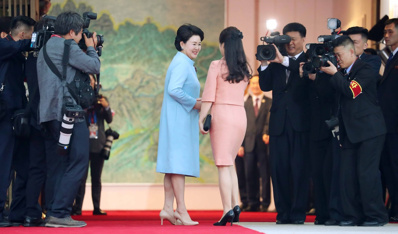The  two Korea's first ladies' first-ever meeting with one another, and the seemingly instant bond they formed. The two wives shake hands before starting the banquet.