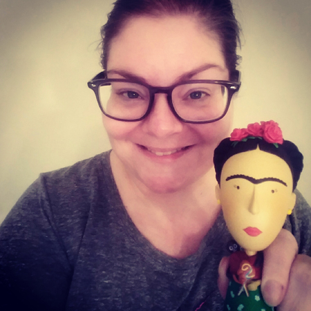 image of me from the shoulders up, smiling while holding a Frida Kahlo figurine