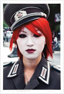 oriental girl in military uniform, pale make-up and dark eyeliner, bright red hair and lipstick.