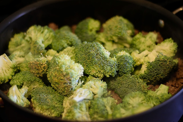 Broccoli being added to the skillet with the browned ground beef.