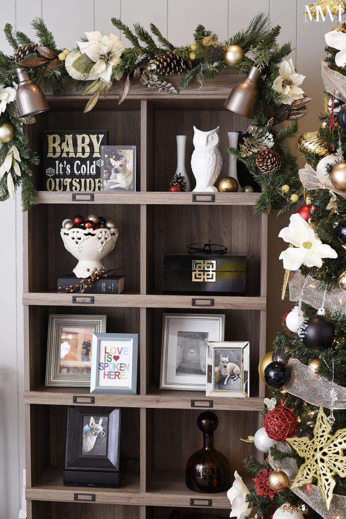 Rustic bookshelf decorated with holiday garland for Christmas decor.