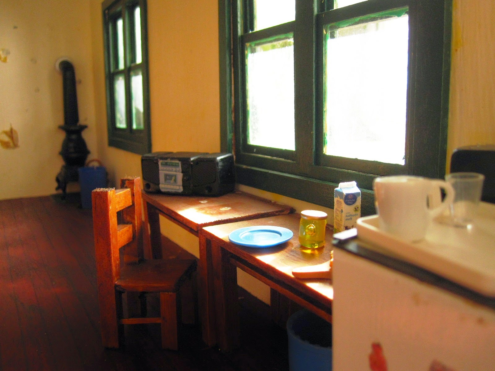 Miniature school house interior with breakfast set up on desks under a sunny window.