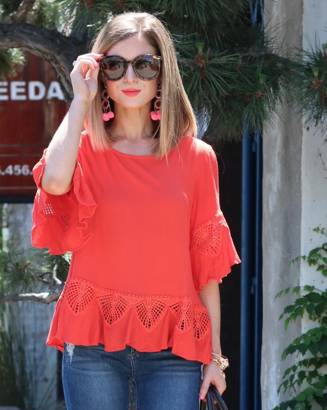Orange top with pom earrings and karen walker tortoise sunglasses.