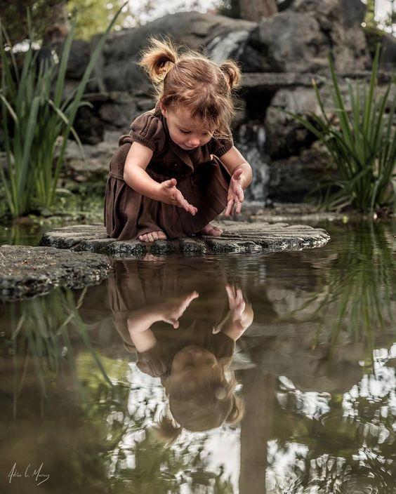 Linda criança, conversa com sua imagem refletida nas águas de um rio.