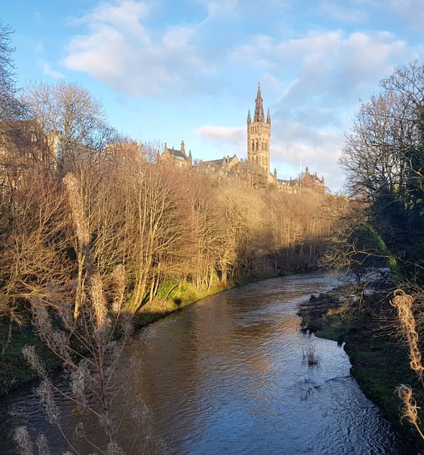 The river Kelvin flows through Kelvingrove Park in winter, with the historic and beautiful Glasgow University building sticking up through the bare trees.