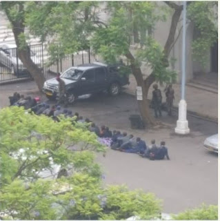 Army in   Zimbabwean Force Policemen To Sit On The Ground After Take Over Pictures of Zimbabwean military operatives disarming policemen and forcing them to sit on the bare ground are trending online.