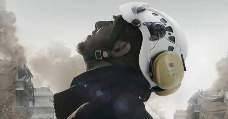 An aid working scans the sky in The White Helmets, a new documentary on Netflix.