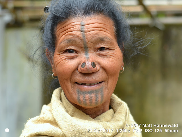 matt hahnewald photography; facing the world; character; face; tattoo; face tattoo; tribal tattoo; eyes; nose; nose plugs; lived-in face; wrinkles; facial expression; eye contact; consent; empathy; emotion; respect; ethnic; traveling; tribal; adivasi; rural; village; traditional; cultural; hong; ziro; arunachal pradesh; northeast india; asian; indian; apatani; one person; female; adult; old; woman; picture; photo; illustrative editorial; face perception; physiognomy; educational; nikon d3100; nikkor af-s 50mm f/1.8g; prime lens; 50mm lens; nifty fifty; 4x3 aspect ratio; horizontal orientation; street; portrait; closeup; headshot; full-face view; outdoors; color; posing; authentic; unique; yaping hullo; yesso; shutterstock; smiling; rapport
