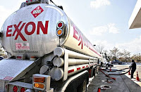 In this Jan. 30, 2009 file photo, an Exxon tanker truck operated by Corey Moorer, right, of Clinton, Md., makes a refueling stop at an Exxon station in Arlington, Va. Exxon Mobil said Monday, Feb. 1, 2010, its fourth-quarter earnings tumbled 23 percent as higher oil prices squeezed profit margins in its refining business. [(Credit: AP Photo/J. Scott Applewhite, file)©AP] Click to Enlarge.