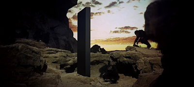Hominids make contact with the Primary Monolith, ape-like hominids, rectangular black monolith on earth, 2001: A space Odyssey, directed by Stanley Kubrick