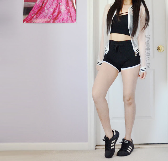 A sporty athletic outfit featuring Dresslink's contrast trim running shorts, a dupe of the American Apparel interlock shorts, worn with a white mesh striped sheer bomber jacket and criss-crossed Brandy Melville style black cropped bralette.