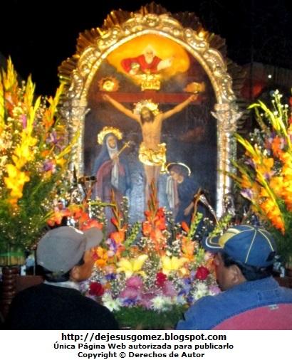Foto colocando flores al Señor de los Milagros.  Foto de Jesus Gómez