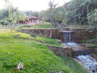 Execução do paredão de pedra, com pedras brutas, na construção do lago com a cascata de pedra com a ponte de madeira. Muro de pedra em Piracaia-SP.