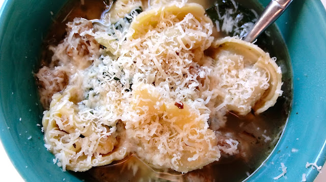 a bowl of Sausage, Spinach, and Fennel Tortellini Soup topped with shredded parmesan