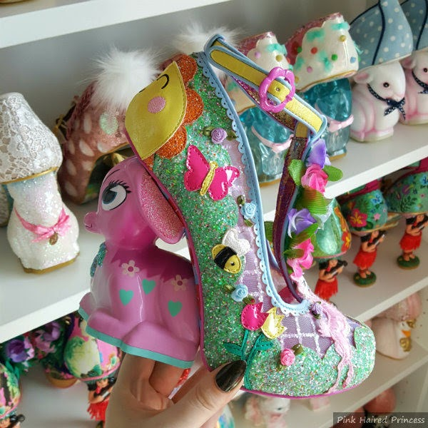 glitter fawn heeled shoe in hand with shoe shelves in background