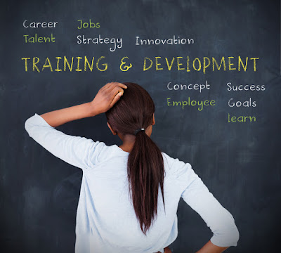 A woman stands in front of a blackboard on which is printed Training and Development