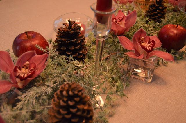 Borddekking med dyprøde lys og orkideer til jul. Nærbilde av blomster og kongler på bordet. Fururlunden DSC_0054