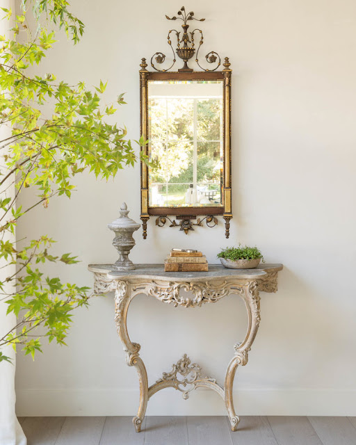 Antique table with gilded mirror in modern farmhouse in California