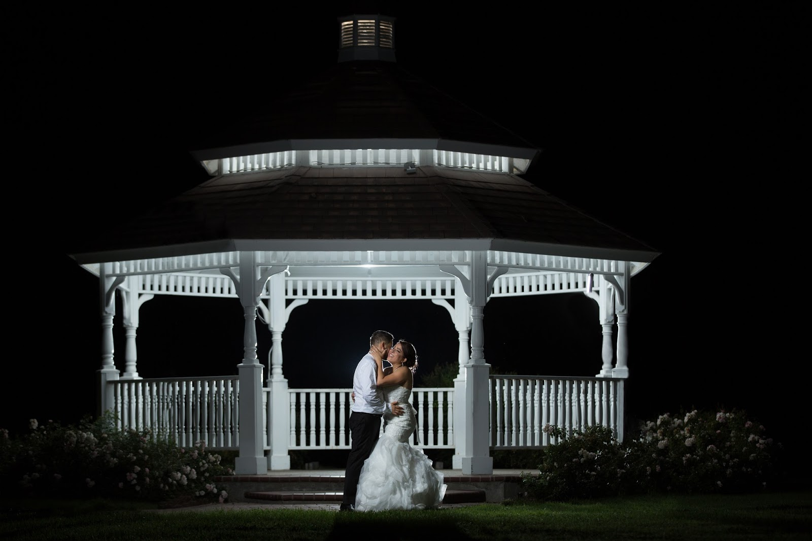 Bride and Groom embrace lovingly under the Gazebo