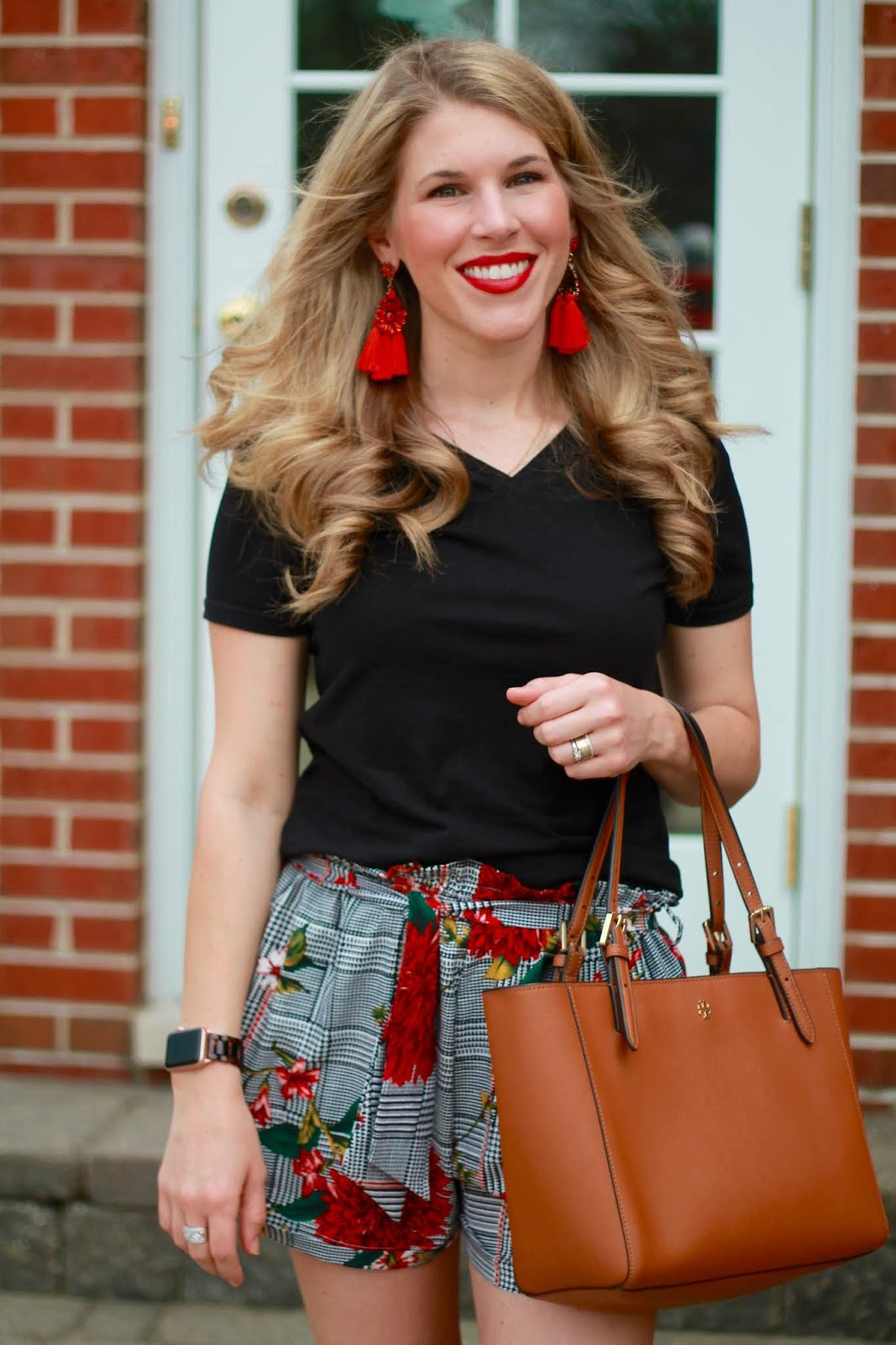 floral and plaid shorts, black tee, red lace up espadrilles, cognac tory burch tote, red tassel earrings,