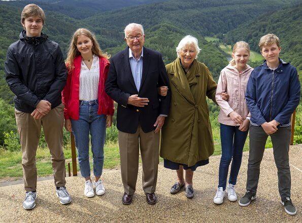 Queen Mathilde, Crown Princess Elisabeth, Prince Gabriel, Princess Eleonore and Queen Paola. beige trench coat white edge trim detail