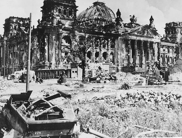 The wrecked Reichstag building in Berlin, Germany, with a destroyed German military vehicle in the foreground, at the end of World War II.