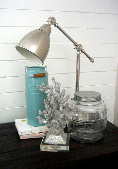 This nightstand with silver accents and a blue tin is decorated cute.