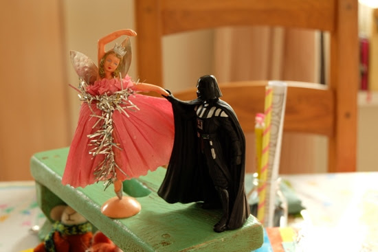 Darth Vader dancing with a fairy on a party table