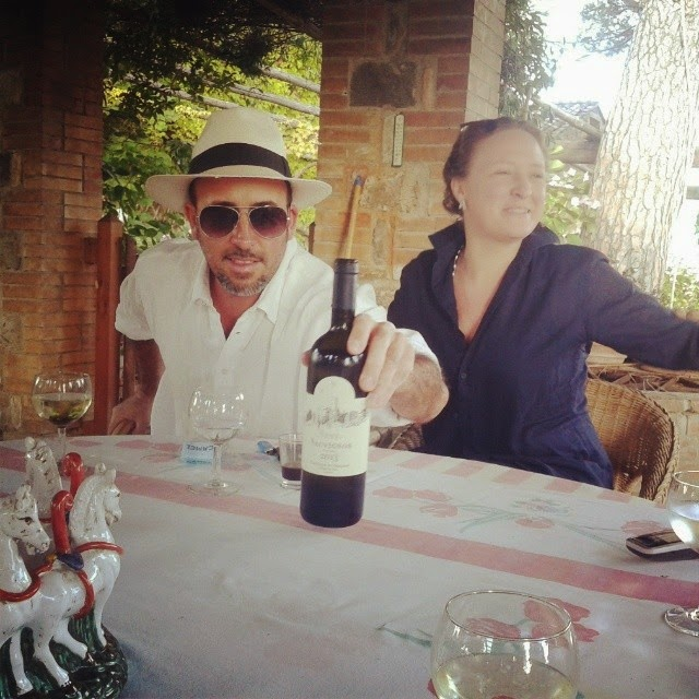 A Tuscan wine producer and a friends at a table with a glass of wine