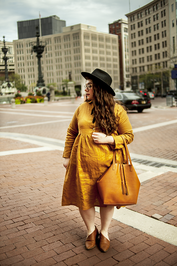 An outfit consisting of a black wide brim hat, an ochre linen baby doll dress, brown tote bag and brown d'oray flats.