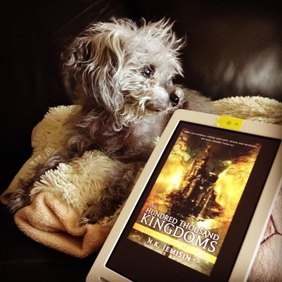 A fuzzy grey poodle, Murchie, lies with his front paws dangling off a sheep-shaped pillow. His head is twisted to peer over the top of a white Kobo with the cover of The Hundred Thousand Kingdoms on its screen. The yellow-toned cover features a massive city perched atop a thing column. An indistinct figure with wild hair hovers in the background.