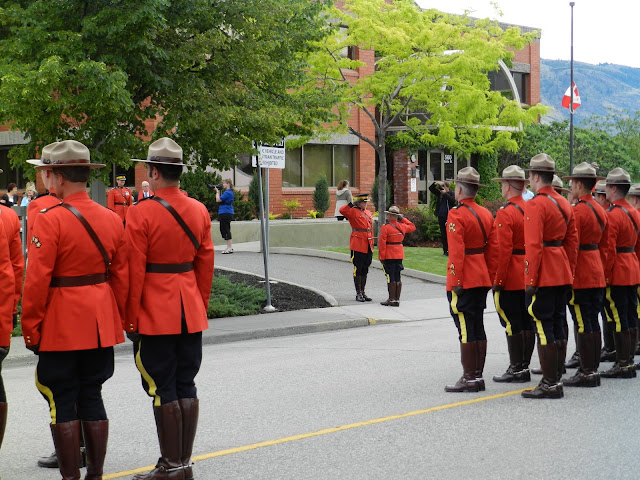 Officers exchange salutes as the others stand at attention