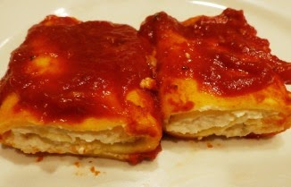 Manicotti on a plate with tomato sauce