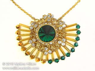 Art deco inspired sunray pendant featuring Aurum and Emerald Swarovski Crystals and long gold bugle beads