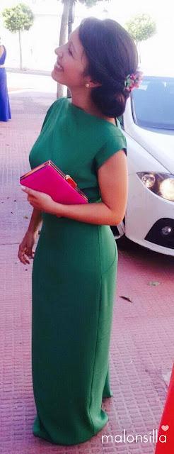 Invitada boda con vestido largo verde esmeralda, bolso clutch en fucsia buganvilla y tocado en recogido bajo de flores preservadas