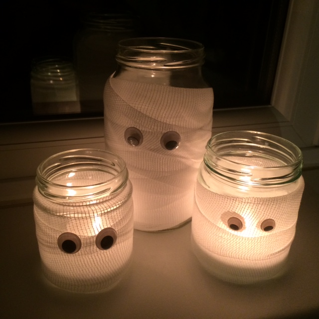 The completed spooky mummy jars lit with tealights